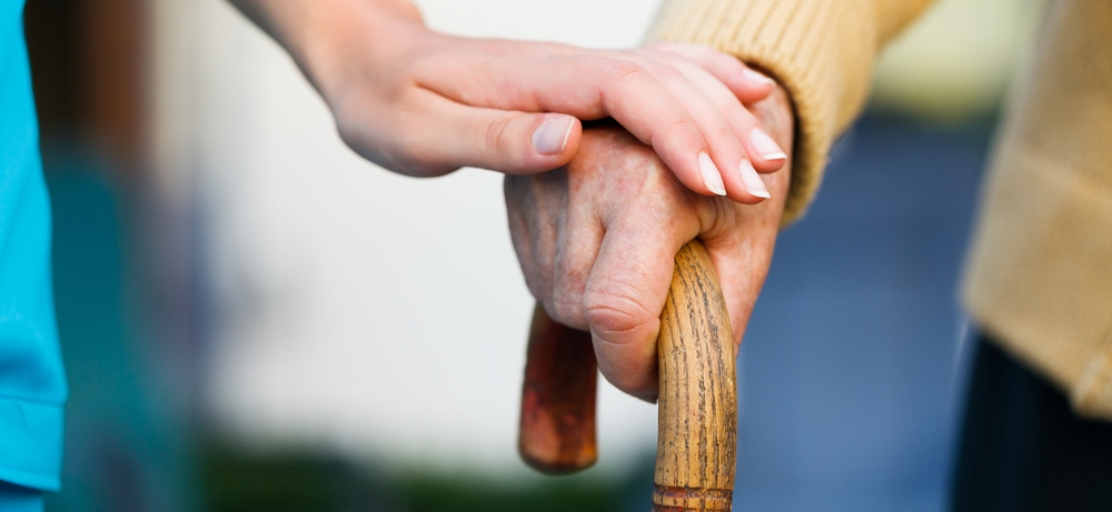 Woman Holding Elderly Man's hand on Cane at Clinton Manor in Breese, IL