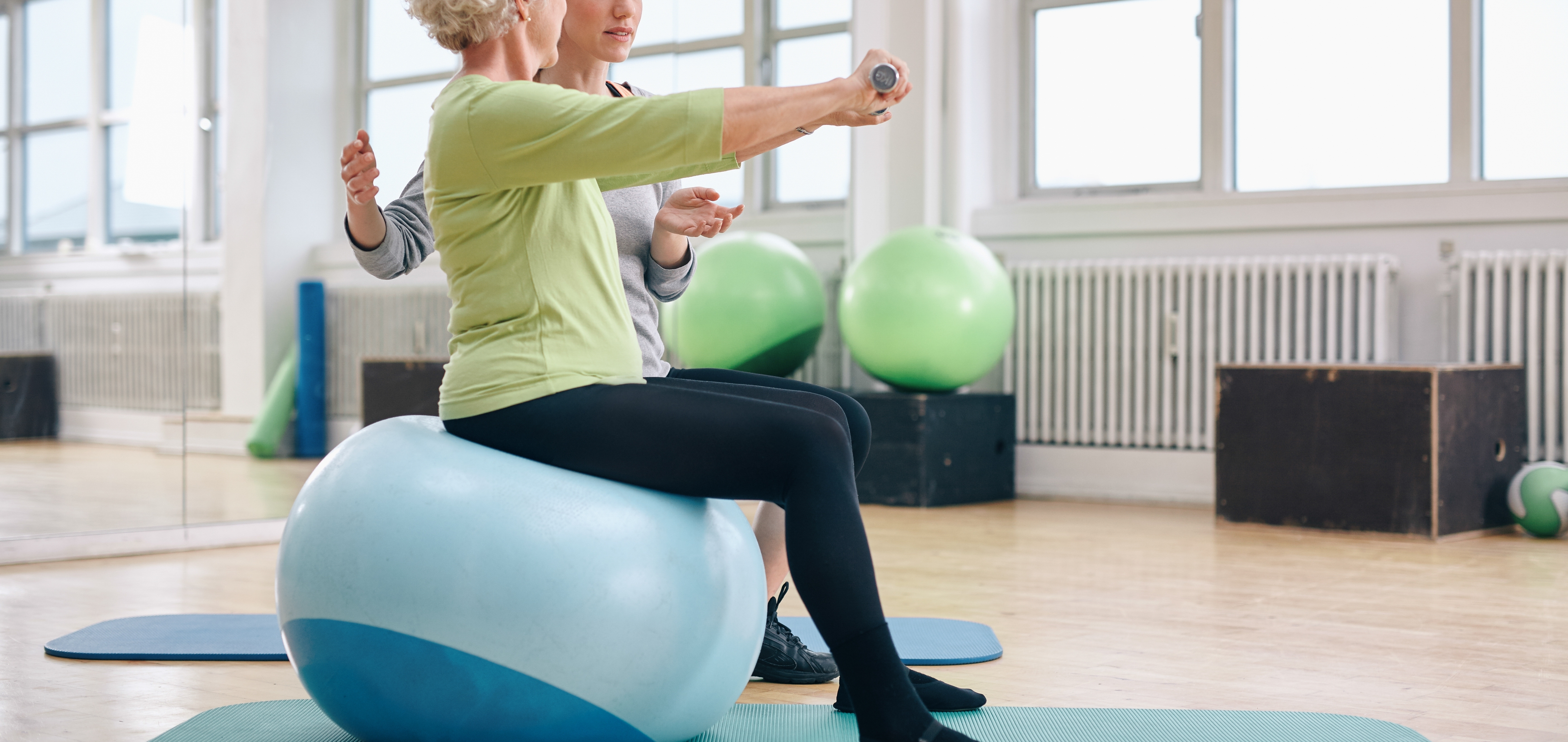 Elderly Lady on Excercise Ball with her Trainer with Weights: Clinton Manor in Breese, IL